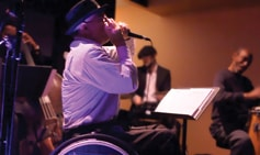 """Frank Barham jams on the chromatic harmonica at The Velvet Note, an Atlanta venue that bills itself as """"designed by musicians for musicians."""""""