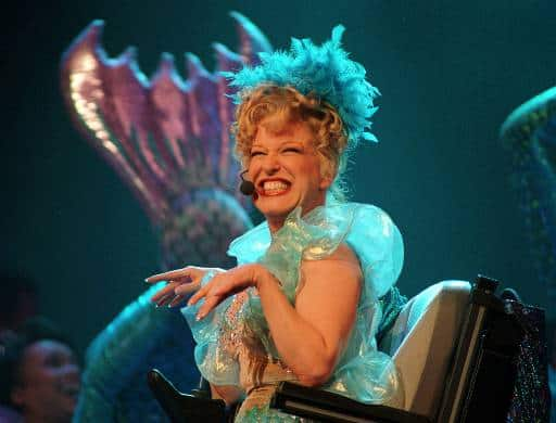 Bette Midler - as Delores De Lago - cavorting on stage in an electric wheelchair.